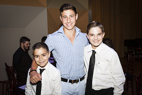 A man in a blue dress shirt poses with two kids at an event