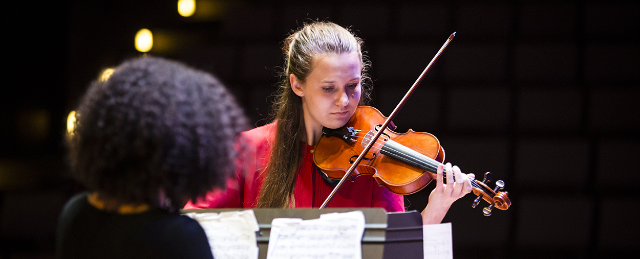 A woman with long blonde hair and red shirt looks down as she plays the violin