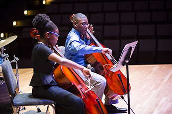 Two well dressed students are sitting down playing cellos as they stare intently at sheet music