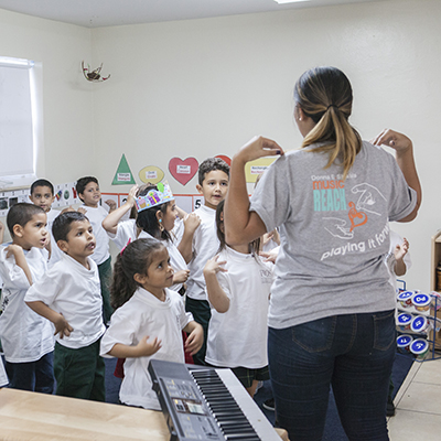 A woman in a gray t-shirt points are her shoulders as she is addressing a group of school children
