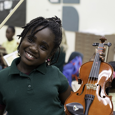 A girl in a green polo shirt smiles while she is holding up a violin