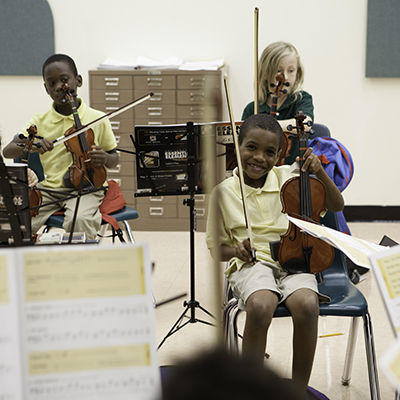 A child smiles while holding up a violin meanwhile others are practicing in the background