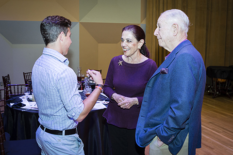 A woman in a purple shirt and a man in a blue jacket speak with another man wearing a blue plaid dress shirt